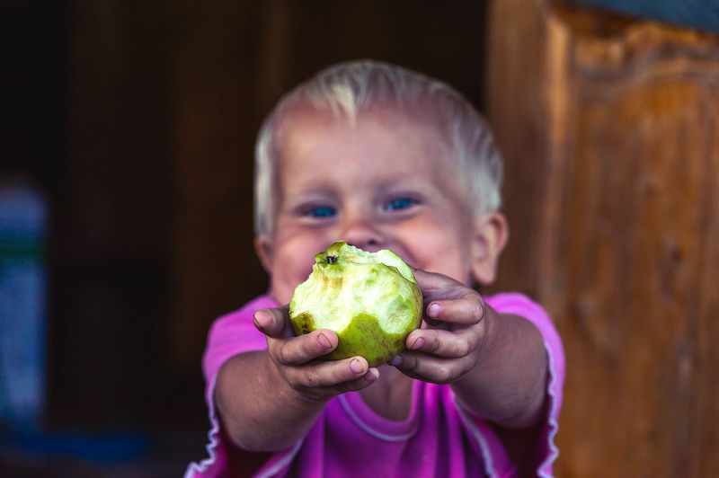 Portrait of smiling boy showing eaten apple