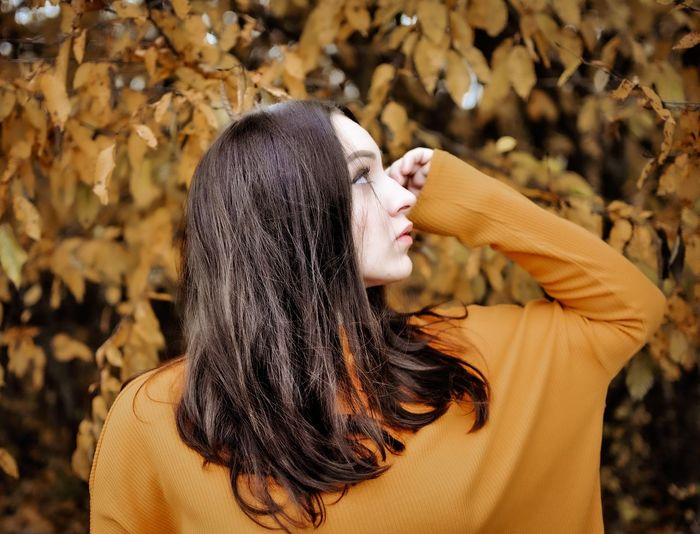 Midsection of woman with leaves during autumn
