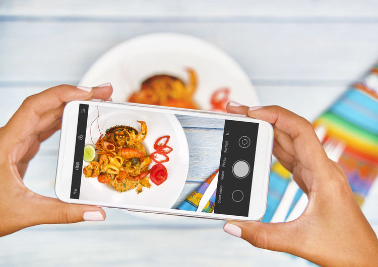 Midsection of person holding mobile phone in plate