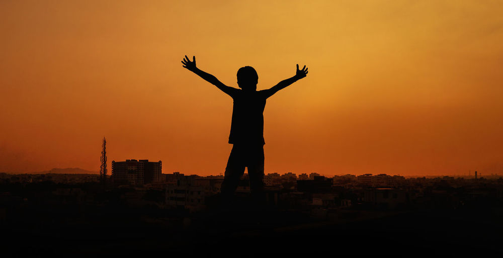 Born to rule Sunset Silhouette Sky Orange Color Human Arm One Person City Built Structure Architecture Building Exterior Arms Outstretched Lifestyles Standing Nature Real People Arms Raised Freedom Outdoors