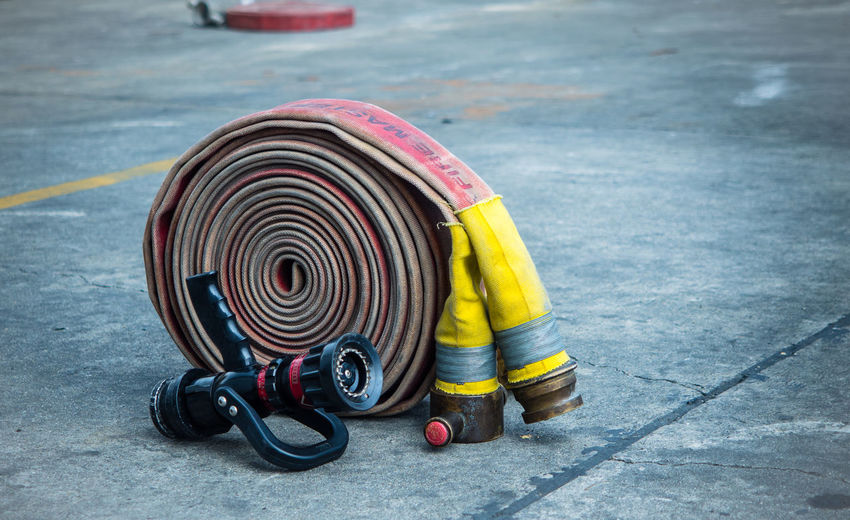 Fire-hose and nozzle on the rough ground Accidents And Disasters City Close-up Day Emergency Equipment Fire Hose Footpath Hose No People Nozzle Outdoors Protection Road Rough Ground Safety Security Sign Street Transportation Urgency Yellow