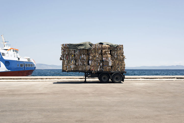 Cardboards on cart by ship in sea against sky