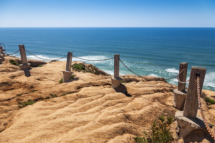 Cliff erosion damaging safety barrier posts and chain on the cliff edge at Torrey Pines, California California Coastline San Diego Cliff Crumble Crumbling Erosion Fence Pacific Ocean Runoff Sandstone Unstable