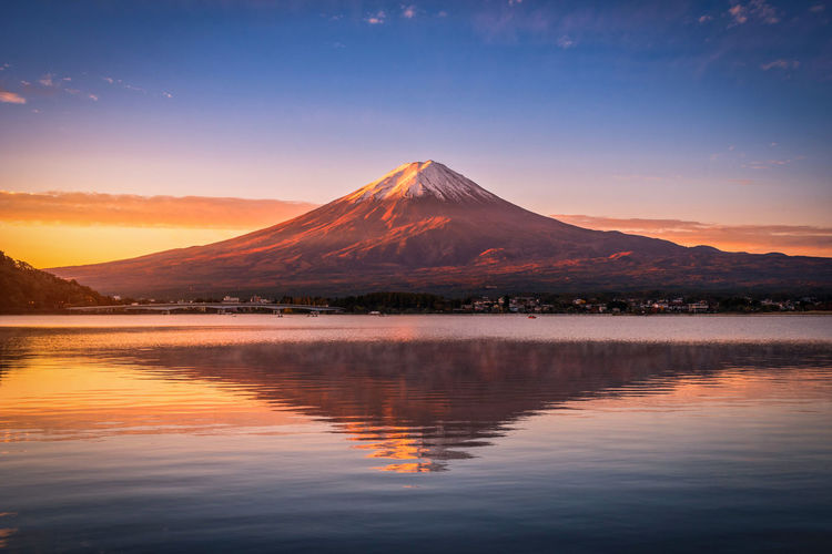 Landscape image of Mt. Fuji over Lake Kawaguchiko at sunrise in Fujikawaguchiko, Japan. Mountain Scenics - Nature Beauty In Nature Water Sky Tranquil Scene Reflection Waterfront Tranquility Lake Nature Idyllic No People Non-urban Scene Sunset Mountain Range Travel Destinations Volcano Landscape Mountain Peak Snowcapped Mountain  Japan Fujikawaguchiko