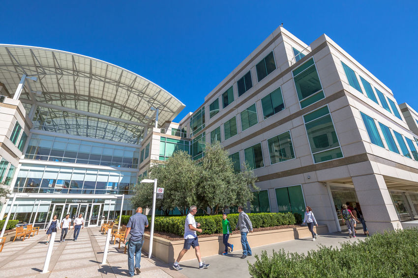 Cupertino, California, United States - August 15, 2016: the Apple world headquarters at One Infinite Loop. Apple is a multinational that produces consumer electronics, personal computers and software. people come from the popular Apple store of Apple Inc Headquarters at One Infinite Loop located in Cupertino, Silicon Valley, California. Apple California IT Mac PC United States Architecture Blue Building Building Exterior Built Structure City Clear Sky Computer Cupertino Day Electronics Industry Flag Headquarter Headquarters Hq IMac27 IPhone Imac Infinite Loop Large Group Of People Men Mobile Modern Outdoors People Real People Sky Store Sunlight Travel Destinations Tree Women