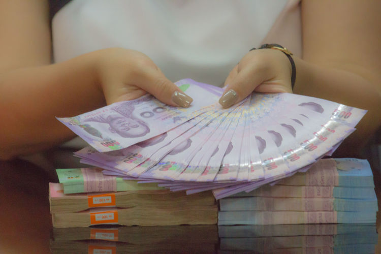 Midsection of woman holding paper currencies