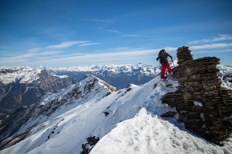 Man Hiking On Snowcapped Mountain Against Sky