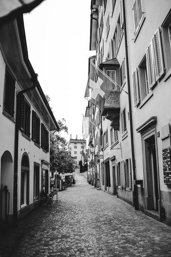 Narrow street between buildings against sky