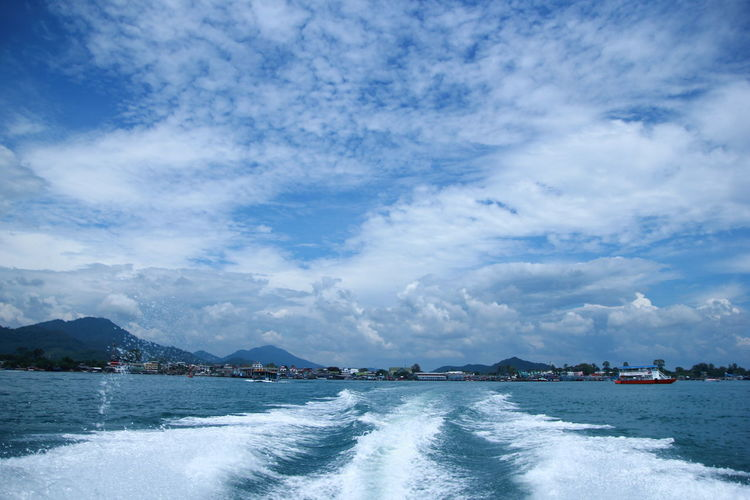 Water Sky Cloud - Sky Beauty In Nature Scenics - Nature Sea Mountain Day Nature Waterfront Motion Tranquility Tranquil Scene Outdoors Wake Nautical Vessel Wake - Water Aquatic Sport Sport No People