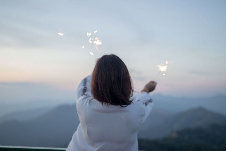 Rear View Of Woman Holding Sparklers Against Sky During Sunset