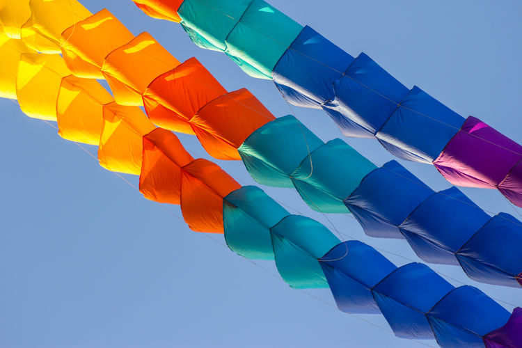Low angle view of multi colored umbrella against blue sky