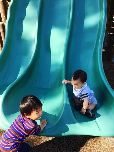 High angle view of siblings playing on slides at park
