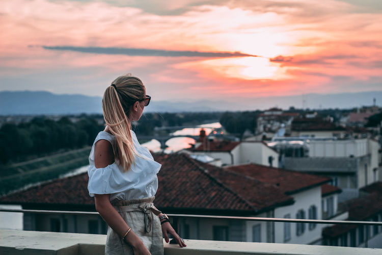 Woman Looking At Cityscape Against Sky During Sunset