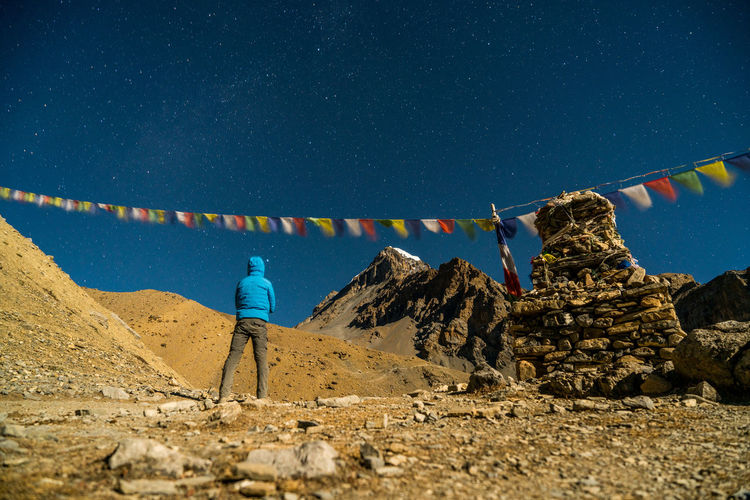 Rear view of hiker standing at annapurna circuit against sky during night
