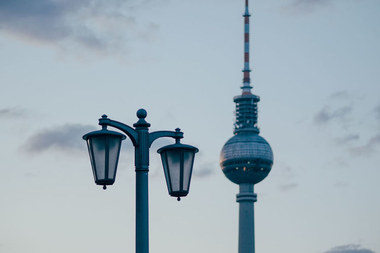 Low angle view of street light against television tower