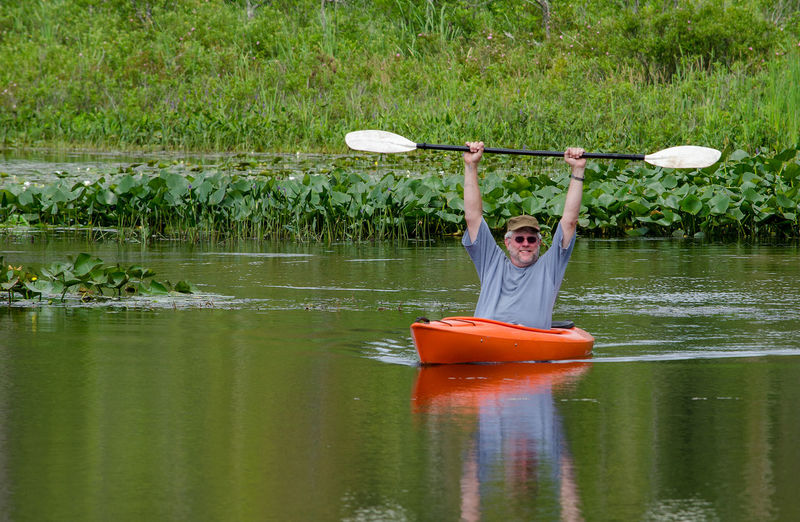 retirement is wonderful! a handsome senior man enjoys retirement by kyaking on a small local pond in Michigan USA Adult Arms Raised Day Front View Holding Human Arm Lake Leisure Activity Lifestyles Men Nature Nautical Vessel Oar Older Male One Person Outdoors Plant Real People Reflection Retirement Senior Male Sport Transportation Victory Water Go Higher Inner Power This Is Aging The Traveler - 2018 EyeEm Awards Summer Sports