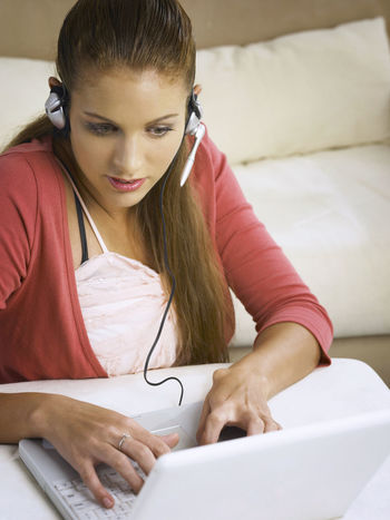 caucasian woman using laptop At Home Online Gaming Blond Hair Casual Clothing Caucasian Charting Communication Computer Connection Ear Phone Indoors  Internet Laptop Listening Microphone One Person Onlline Real People Sitting Technology Telecommunications Equipment Using Laptop Wireless Technology Young Adult Young Women