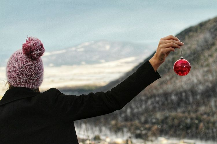 Rear View Of Woman Holding Red Bauble On Mountain During Winter