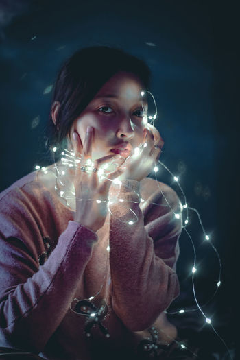 Portrait of beautiful young woman holding illuminated string lights while sitting against wall