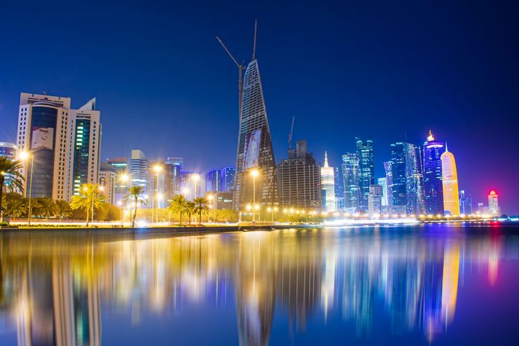 Illuminated buildings by river against blue sky at night