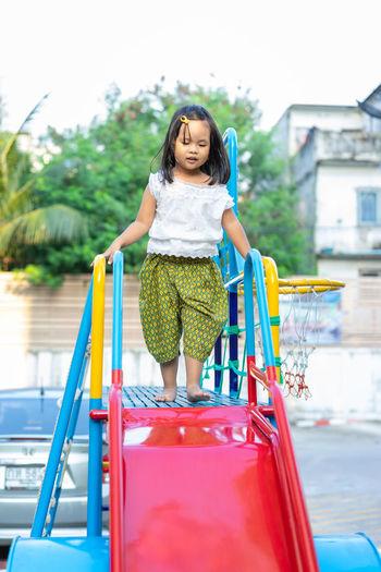Full length of girl walking on slide in playground