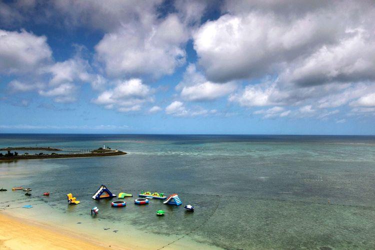 Beach toys at calm sea against the sky