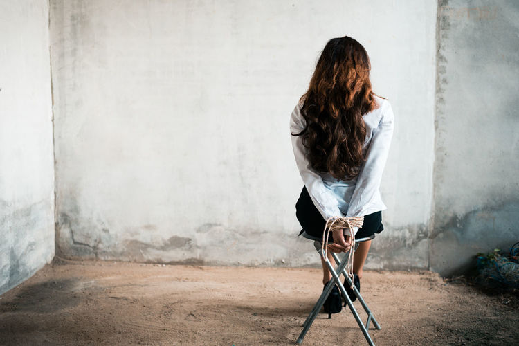Rear view of woman with tied hands sitting on chair