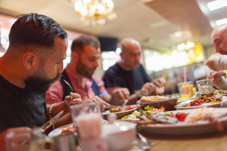 Middle Eastern men enjoying a traditional Iftar dinner. Selective focus Arabian Eating Food And Drink Fun Iftar Males  Man Ramadan  Suhoor Arab Fast Fasting Food Food And Drink Friendship Male Men Muslim People Ramazan Real People Restaurant Syrian Together Togetherness