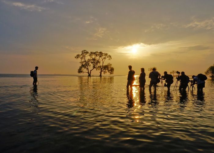 People And Places Sun Sunset Silhouette Water Reflection Beauty In Nature Sunrise Sea Nature Sky Togetherness Calm Seascape Vacations Person Majestic Waterfront Untungjawa Tree Silhouette INDONESIA Done That.