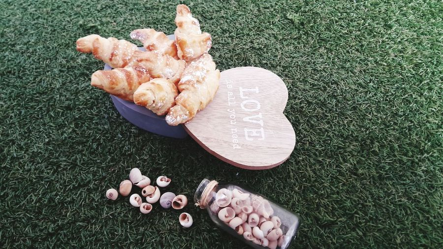 High angel view of croissants in container by heart shape with shells over field