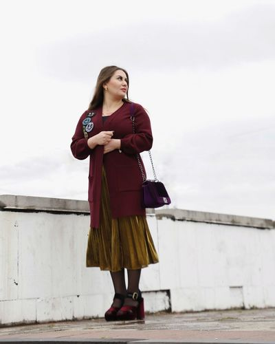 Full length of young woman looking away against sky