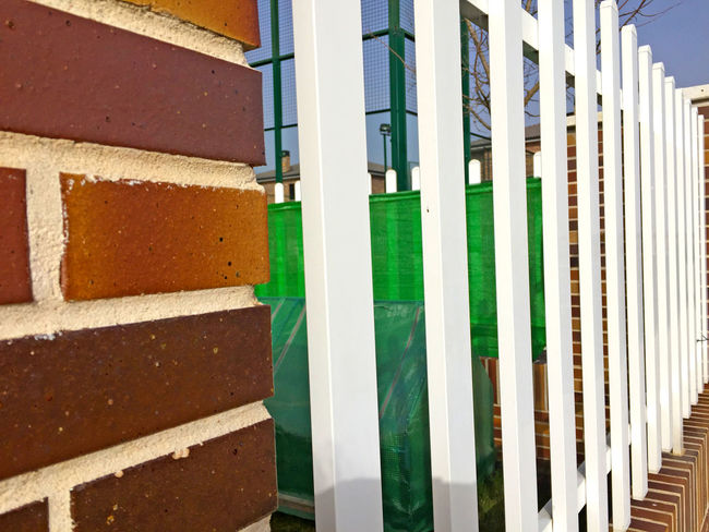 Architecture Architecture Backgrounds Brick Brick Wall Building Building Exterior Buildings Built Structure Close-up Construction Day Fence From My Point Of View Green Color Metal Metallic Fence No People Outdoors Textured  Textures And Surfaces Wallpaper White Fence