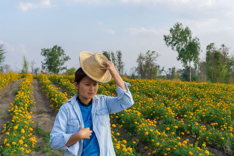 Girl watching yellow marigold flowers. One Person Plant Real People Front View Child Growth Childhood Nature Standing Hat Beauty In Nature Waist Up Males  Leisure Activity Boys Land Tree Day Clothing Yellow Outdoors Human Arm Arms Raised Pre-adolescent Child Marigold Marigold Flower Marigold Farm Marigold Garden