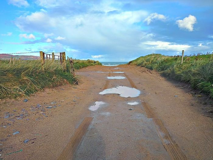 Sandpath Beach Path Landscape Sea Outdoors Sky Nature Beauty In Nature Puddles Grass Fence Clouds