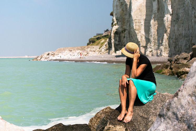 Woman sitting on rock on beach
