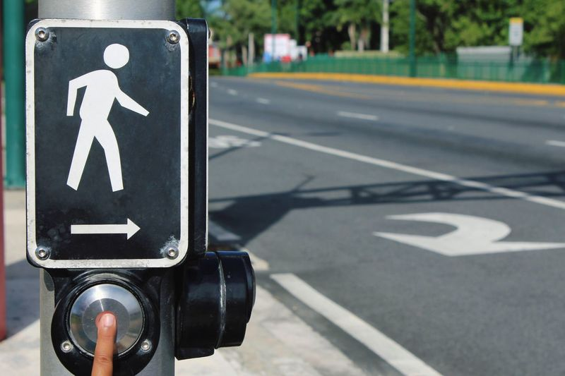 Cropped finger of person pressing button below crossing sign