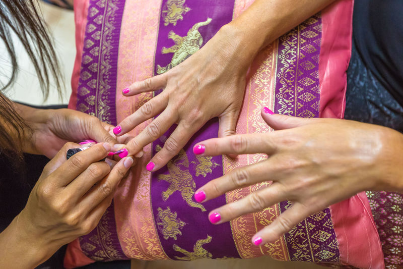 Cropped Hands Of Woman Applying Nail Polish On Customer Hand