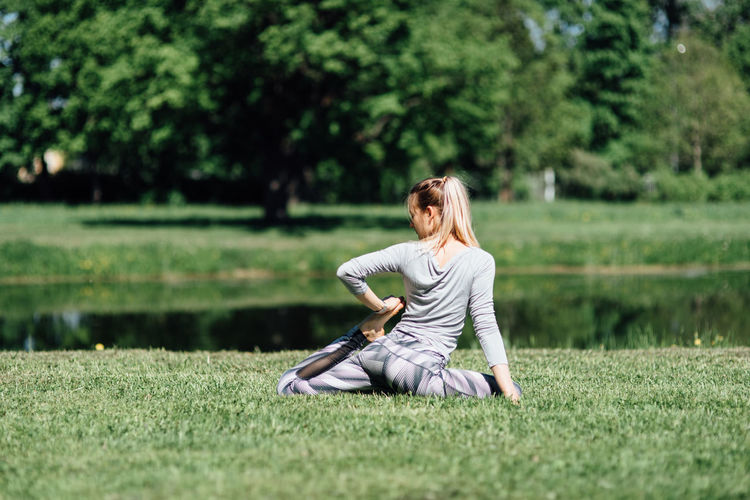 Young woman exercising by pond on field