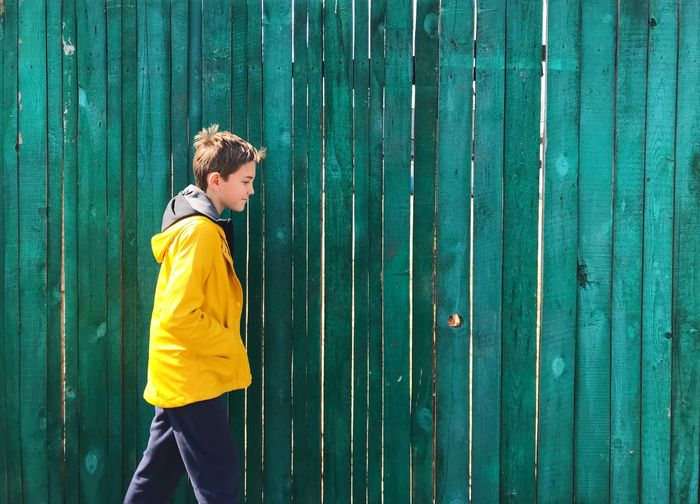 Side view of boy looking away against blue wall