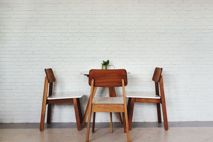 Empty chairs and table against brick wall at cafe
