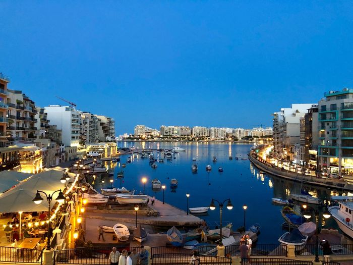High angle view of illuminated harbor by buildings against blue sky