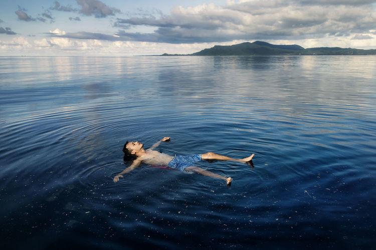 A man floating on water at karimunjawa island, jepara, central java, indonesia