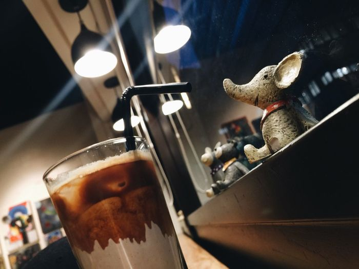 Close-up of cold coffee by animal figurines
