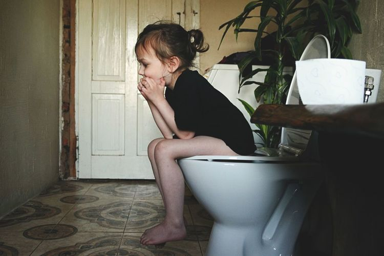 Side view of girl sitting on toilet bowl in bathroom at home