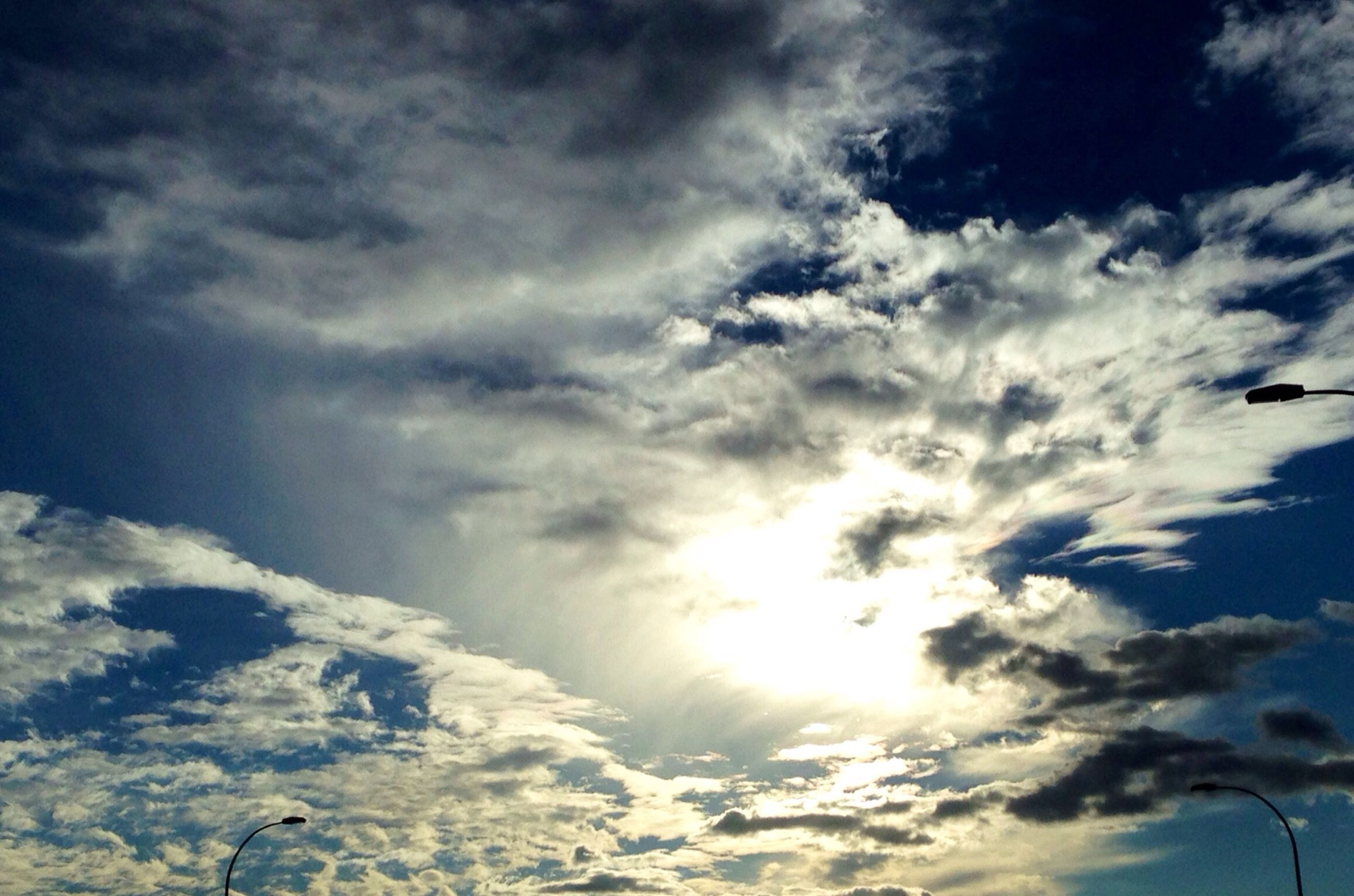 low angle view, sky, cloud - sky, beauty in nature, cloudy, scenics, nature, tranquility, sky only, sun, cloud, sunbeam, cloudscape, tranquil scene, sunlight, blue, idyllic, outdoors, no people, day