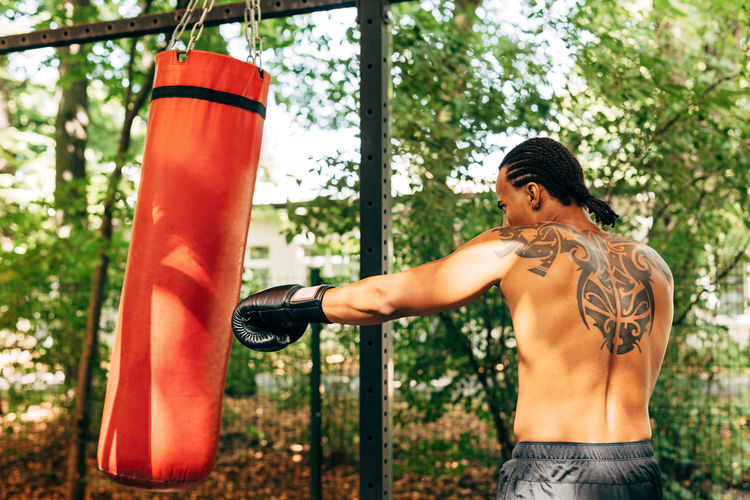 Rear view of shirtless man boxing while standing against tree