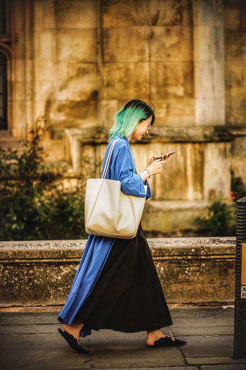 Side view of woman using mobile phone while walking on street