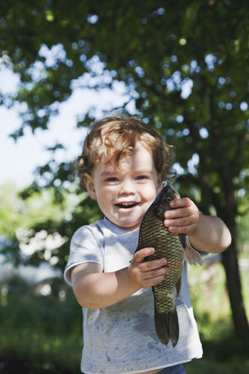 Full length of boy holding baby while standing against trees