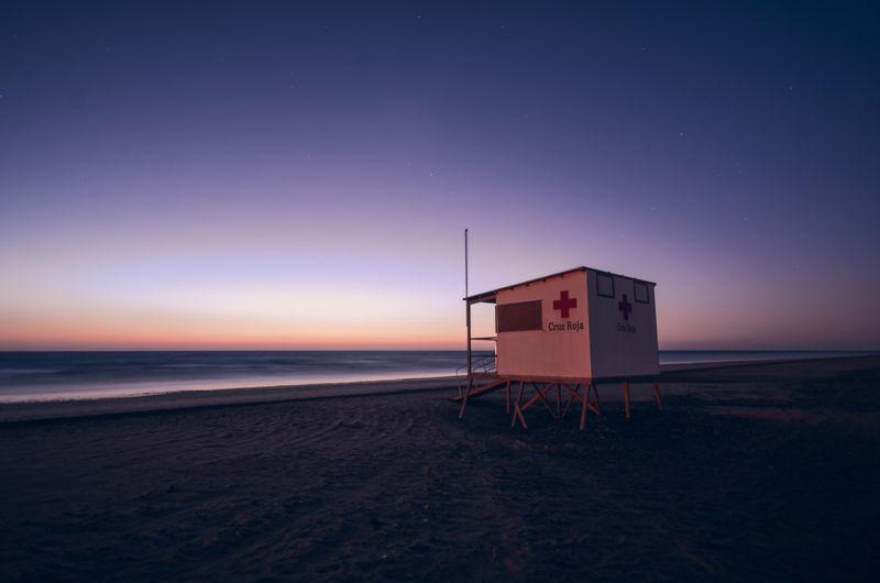 Hut on beach against sky during sunset