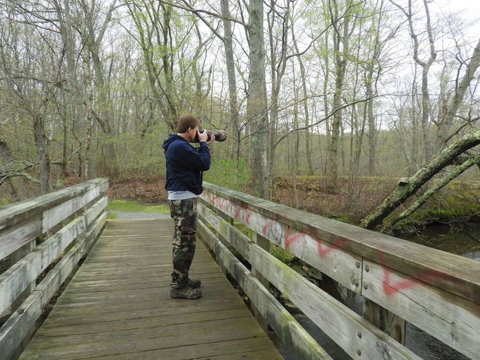 One Man With A Camera Bird Watching Birds Wildlife Nature Calm Tranquility Tranquil Scene Outdoors Beauty In Nature Nature Photography Tree Full Length Standing Stream Tranquil Scene Footbridge
